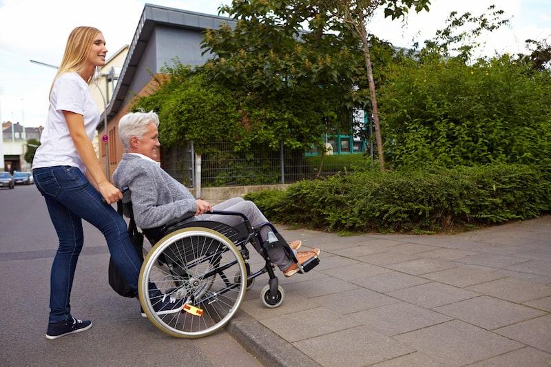 Andere-Teilnehmer-Strassenverkehr-Frau-hilf-Mann-im-Rollstuhl-ueber-Strasse.jpeg
