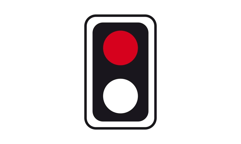 Vor einem Bahnübergang steht vor einer von rechts einmündenden Straße ein rot leuchtendes Lichtzeichen ohne Andreaskreuz. Wo müssen Sie warten?